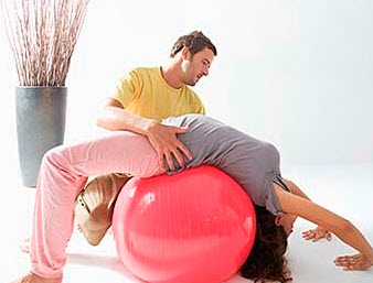 A chiropractor using a training ball